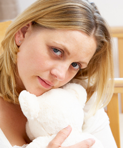 Image of mother of stillborn baby hugging teddy bear