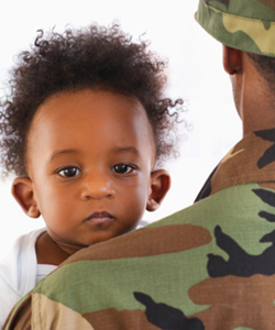 Injured Baby looking over Army dad shoulder